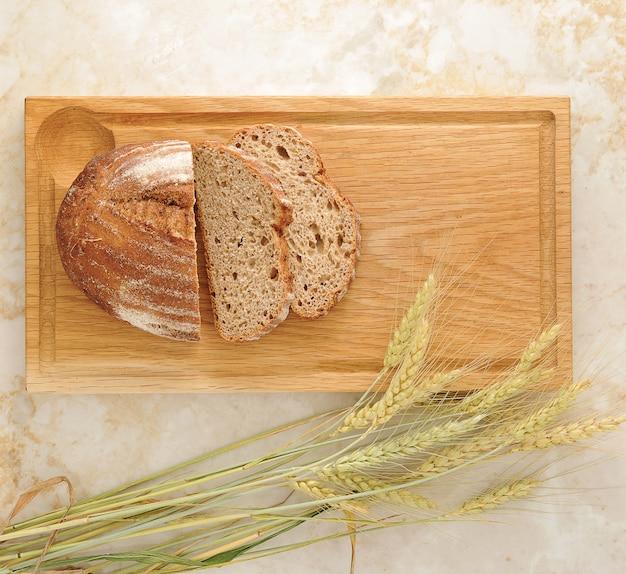 Orecchie del grano e del pane sul bordo di legno