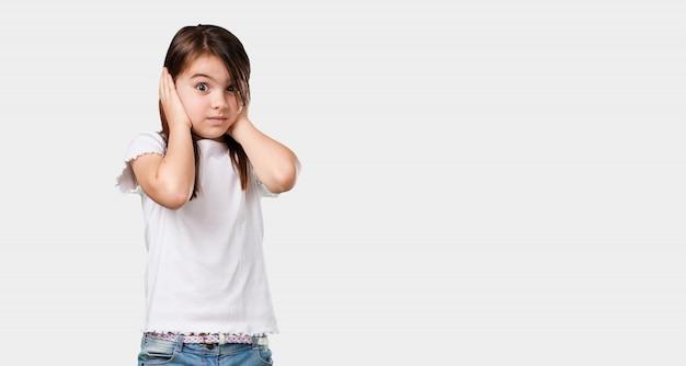 Orecchie della copertura della bambina del corpo pieno con le mani, arrabbiate e stancate di sentire un certo suono
