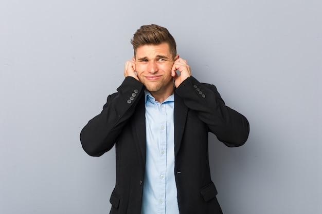 Orecchie di copertura di giovane uomo caucasico bello con le mani.