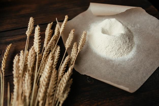 Orecchie e farina di grano su carta da lucido su un fondo di legno scuro