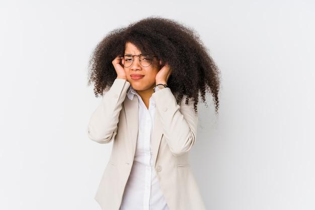Orecchie giovani della copertura della donna di affari con le mani