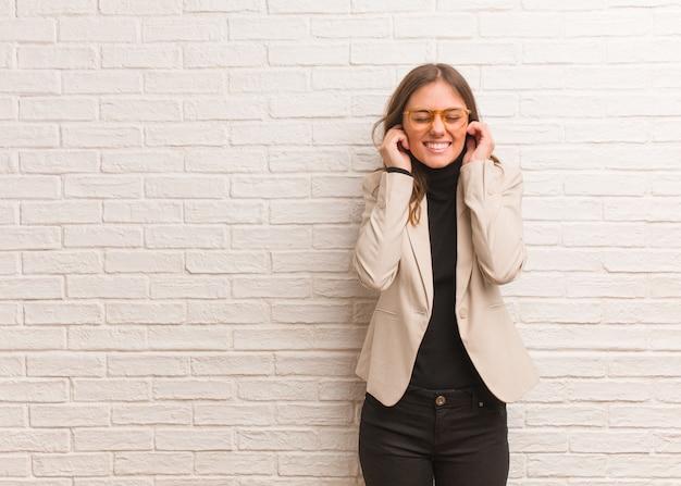 Orecchie graziose giovani della copertura della donna dell'imprenditore di affari con le mani
