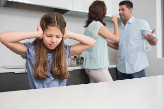 Orecchie tristi della copertura della ragazza mentre genitori che litigano nella cucina