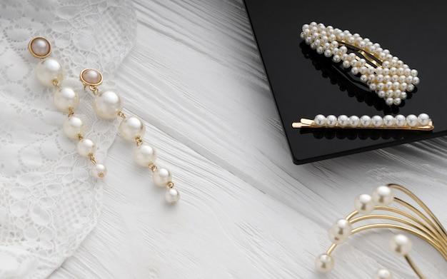 Orecchini, bracciale e forcine in oro e perle su superficie di legno