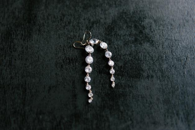 Orecchini d'argento delle donne eleganti su una priorità bassa nera