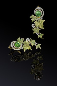 Orecchini di lusso in oro giallo con demantoidi verdi e diamanti isolati su sfondo nero con riflessione, percorso di clipping incluso. estremo da vicino.