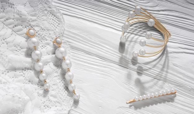 Orecchini e bracciale di perle dorate su legno bianco