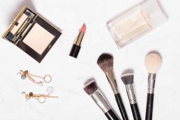 Orecchini e cosmetici su bianco