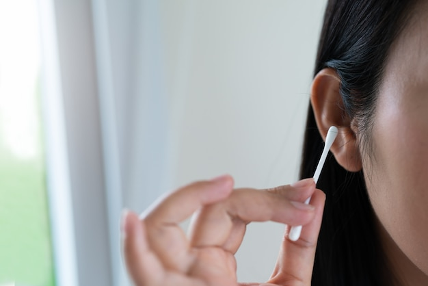 Orecchio di pulizia donna con un batuffolo di cotone