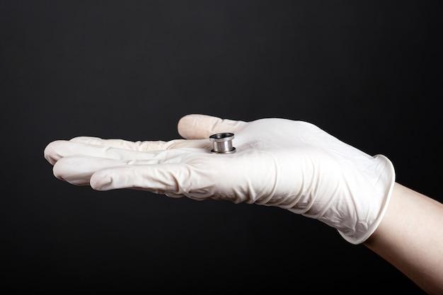 Orecchio gioielli, tunnel per le orecchie color argento in mano su uno sfondo scuro.