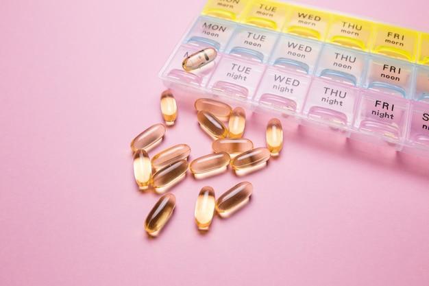 Organizzatore per le pillole mediche su un primo piano del fondo isolato rosa. organizzazione di assunzione di pillole del giorno. vitamine trasparenti si trovano nelle vicinanze.