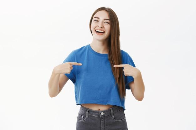 Orgogliosa donna europea attraente in maglietta blu con lunghi capelli castani sani che ride con gioia e punta con orgoglio a se stessa che vuole essere candidata, sorridente amichevole