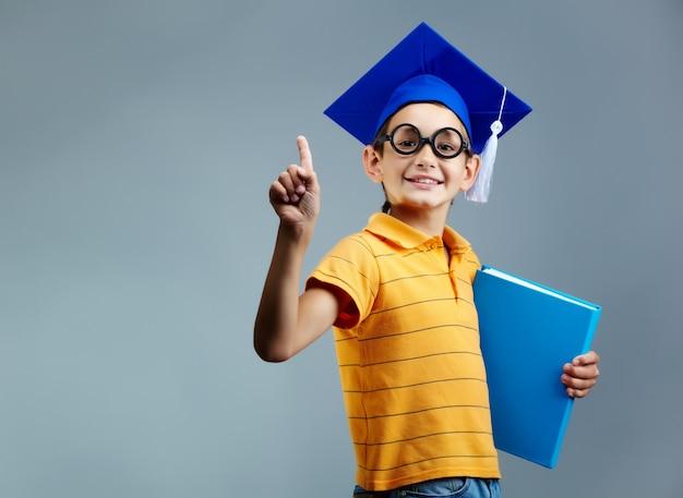 Orgoglioso ragazzino con gli occhiali e cappello di laurea