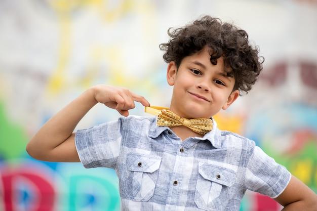 Orgoglioso ragazzo che punta al suo papillon