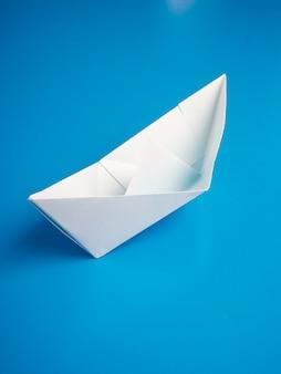 Origami concetto di business carta bianca barca minima su sfondo blu