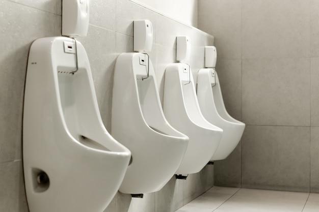 Orinatoi bianchi di fila nella toilette pubblica degli uomini.