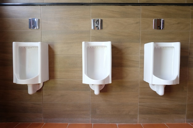 Orinatoi bianchi nel bagno degli uomini di decorazione d'interni.