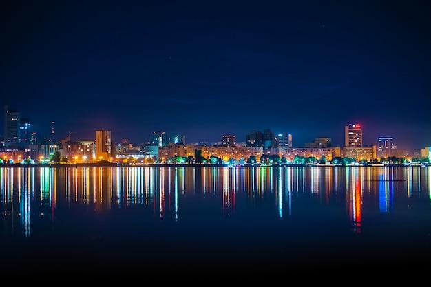 Orizzonte notturno della città con molte luci colorate riflesse nell'acqua