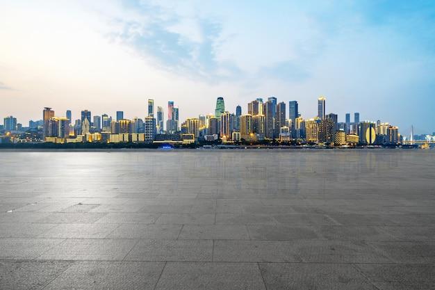 Orizzonte panoramico ed edifici con pavimento quadrato di cemento vuoto