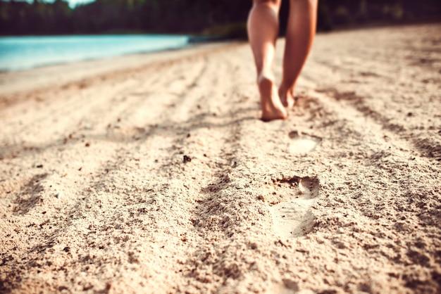 Orme sulla sabbia con le gambe della ragazza che cammina