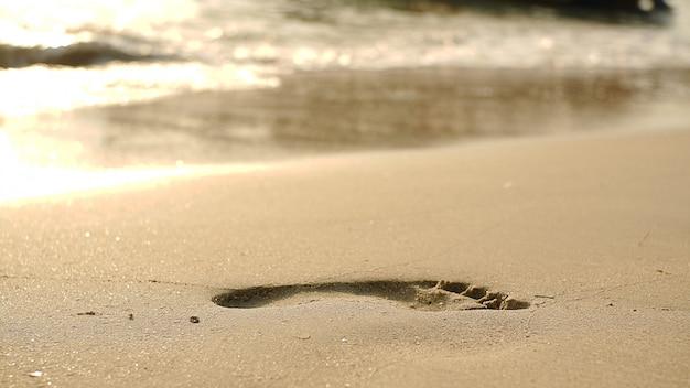 Orme sulla spiaggia di sabbia e onde in aumento