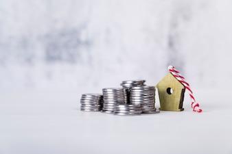 Ornamenti del Birdhouse con la pila di monete sulla superficie di bianco