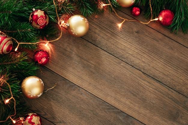 Ornamenti di natale e rami di pino su un tavolo di legno. vacanze di natale. copyspace. vista dall'alto
