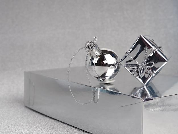 Ornamenti e regalo d'argento di natale sulla vista superiore della priorità bassa d'argento. palle di natale argento