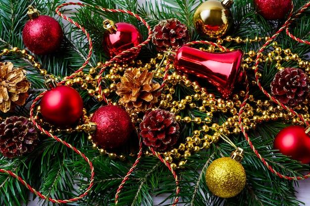 Ornamenti rossi di natale con i branelli dorati e le filiali dell'abete