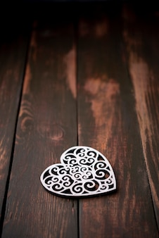 Ornamento a forma di cuore su fondo di legno