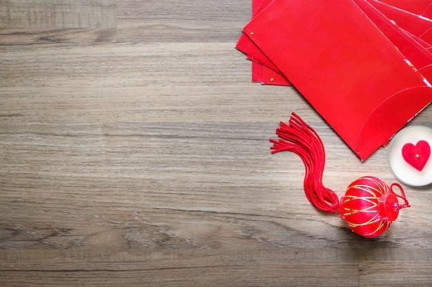 Ornamento cinese del nuovo anno, lanterna cinese fortunata rossa e busta rossa su fondo di legno