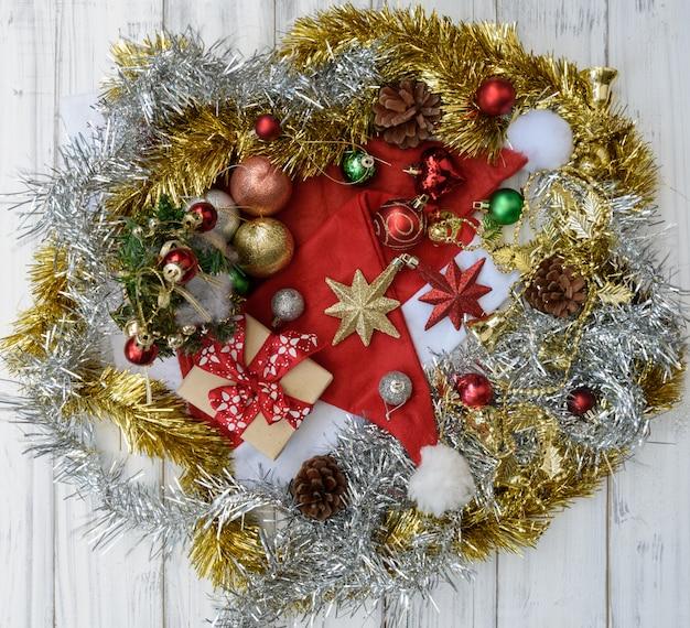 Ornamento di natale decorativo con cappello da babbo natale, scatole regalo, stella, pigne su fondo di legno bianco, piatto laici