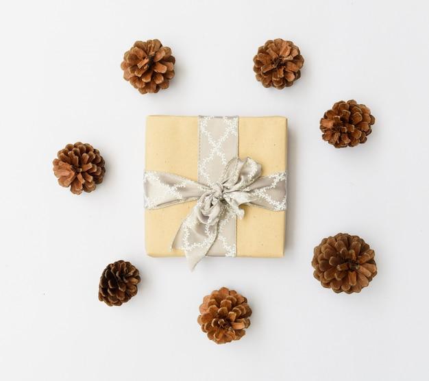 Ornamento di natale scatola regalo marrone e pigne su sfondo bianco, piatto laici