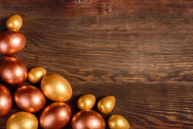 Oro e bronzo delle uova di pasqua su fondo di legno