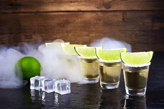 Oro messicano tequila in bicchieri corti con sale, fette di lime e ghiaccio su un tavolo di legno. fumo.