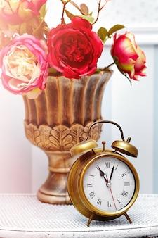 Orologio classico orologio in interni retrò colorati luminosi dietro fiori rossi
