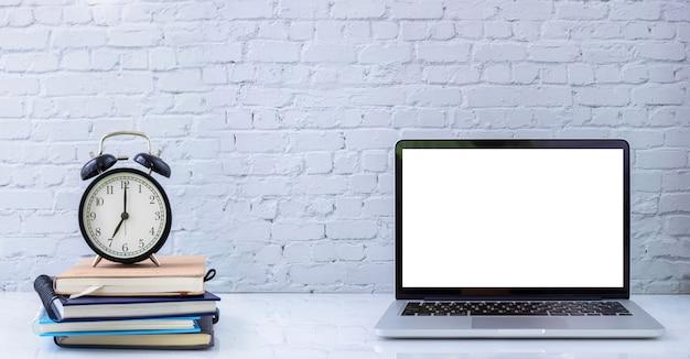 Orologio classico sulla pila di libro e sul computer portatile dello schermo in bianco, taccuino con struttura bianca del muro di mattoni