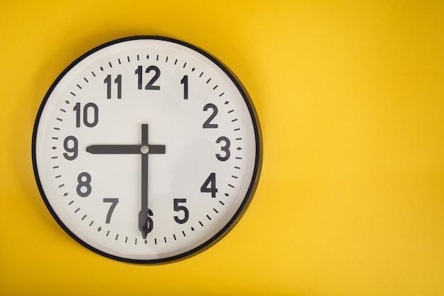 Orologio da parete sul muro giallo. copyspace