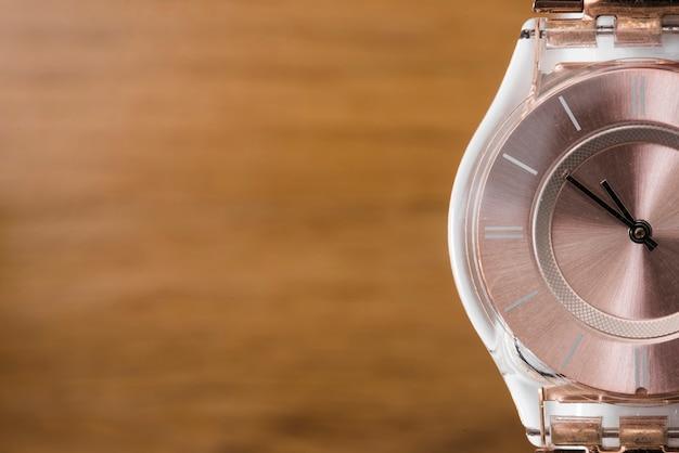Orologio da polso di lusso su sfocatura dello sfondo in legno con texture