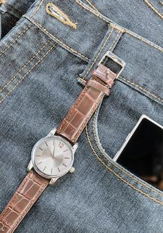 Orologio da polso e smartphone su jeans