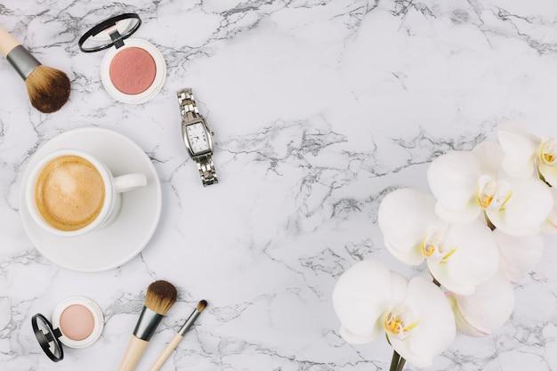 Orologio da polso; tazza di caffè; polvere compatta; spazzola di trucco e fiore dell'orchidea su priorità bassa di marmo