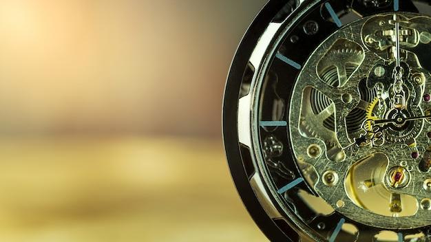 Orologio da tasca del primo piano sulla tavola e sulla luce solare.