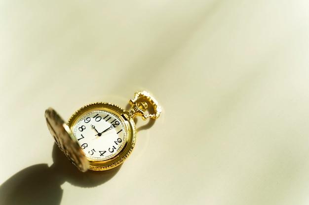 Orologio da tasca dorato sul tavolo con luce solare