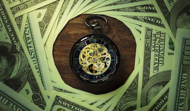 Orologio da tasca e banconota del dollaro che impilano nel fondo di oscurità