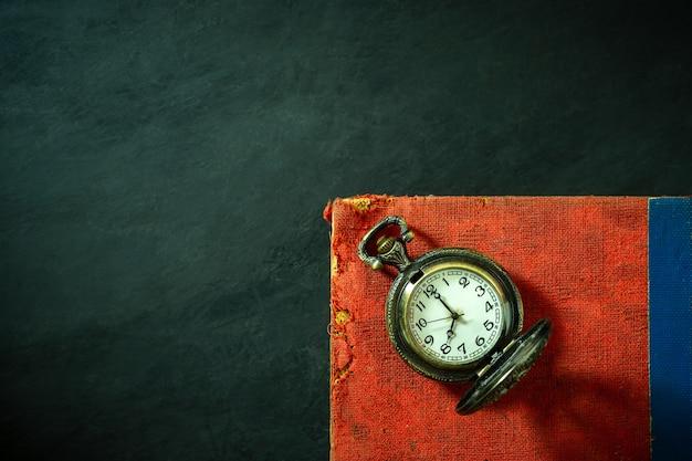 Orologio da tasca e vecchio libro sul pavimento di cemento.