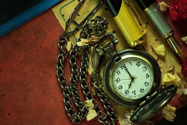 Orologio da tasca vintage e penna in ottone sul vecchio libro. alle 8 di mattina. vista dall'alto e copia spazio. istruzione e concetto di stile vintage.
