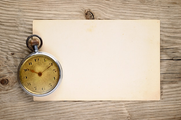 Orologio da tasca vintage e vecchia cartolina su legno