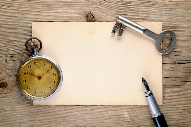 Orologio da tasca vintage, penna stilografica, chiave e vecchia cartolina