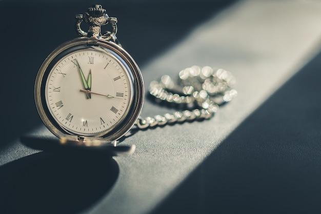 Orologio da tasca vintage sulla catena su uno sfondo scuro