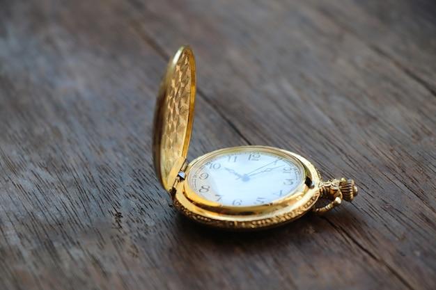 Orologio da taschino dorato design classico orologio 10.10 ore su sfondo tavolo in legno